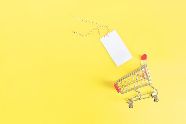 Carrinho de supermercado com rótulo preto vazio sobre fundo amarelo.