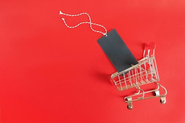 Carrinho de supermercado com rótulo preto vazio sobre fundo vermelho.