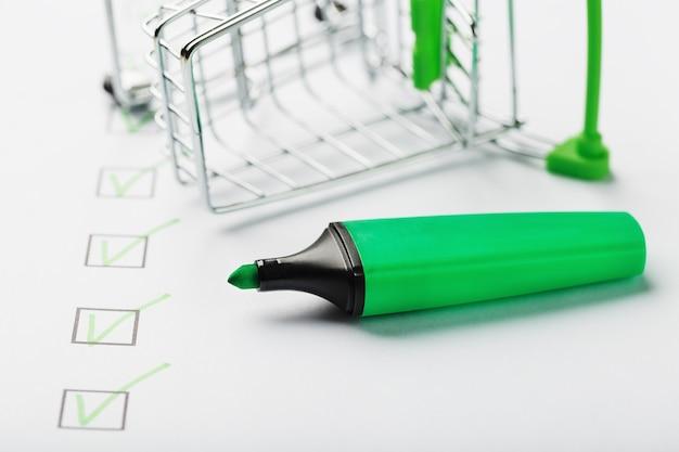 Carrinho de supermercado e marcador verde marcados na folha da lista de verificação. conceito de tarefa concluída de lista de verificação de compras.