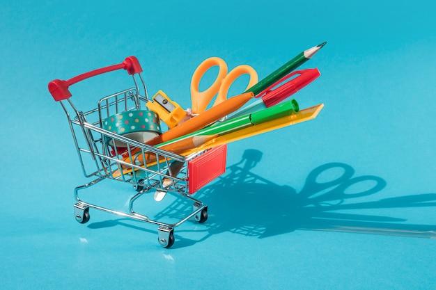 Carrinho de supermercado em miniatura com papelaria no interior: tesouras, canetas, lápis, clipes de papel, régua, fita adesiva. fundo azul, copyspace.