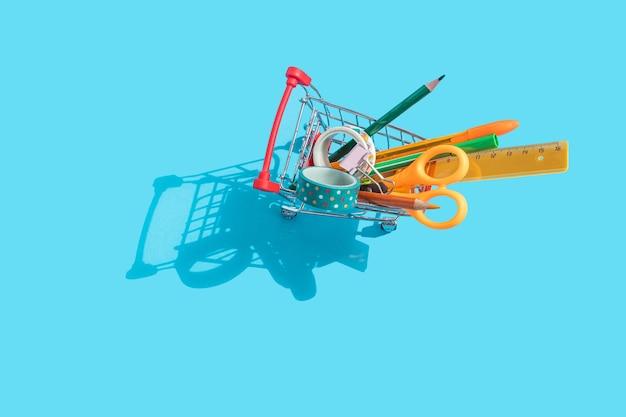 Carrinho de supermercado em miniatura com papelaria no interior: tesouras, canetas, lápis, clipes de papel, régua, fita adesiva. fundo azul, vista superior, postura plana.