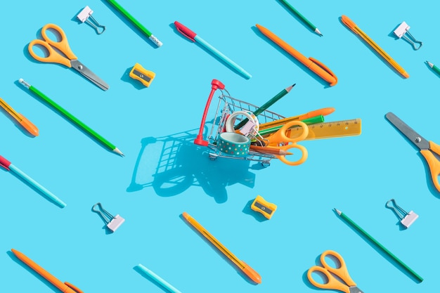 Carrinho de supermercado em miniatura com papelaria no interior: tesouras, canetas, lápis, clipes de papel, régua, fita adesiva. os mesmos objetos estão espalhados. fundo azul, vista superior, postura plana.