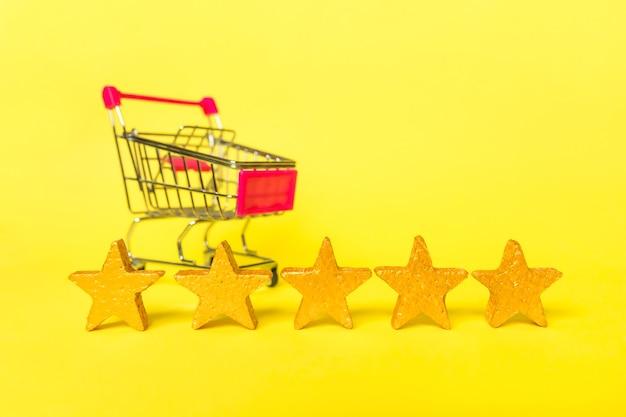 Carrinho de supermercado para compras com estrelas douradas, classificação isolada em fundo amarelo