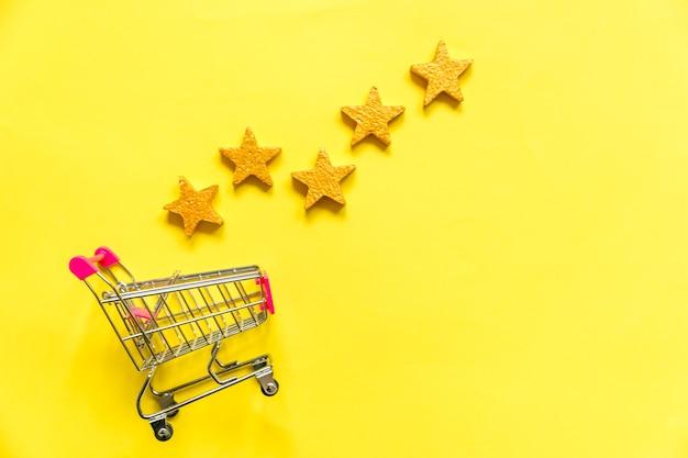 Carrinho de supermercado para compras com rodas e classificação com estrelas douradas isoladas em amarelo