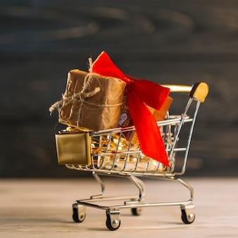 Carrinho de supermercado pequeno com caixa de presente com faixa vermelha
