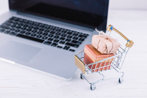Carrinho de supermercado pequeno com caixas de presente e laptop