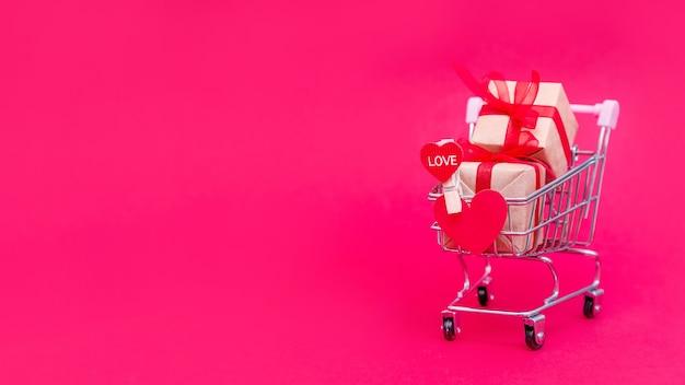 Carrinho de supermercado pequeno com caixas de presente em uma superfície rosa vermelha