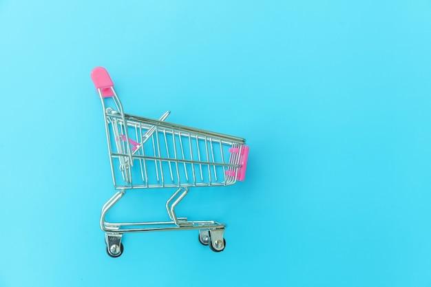 Carrinho de supermercado pequeno para compras de brinquedo com rodas isoladas em azul pastel colorido moderno