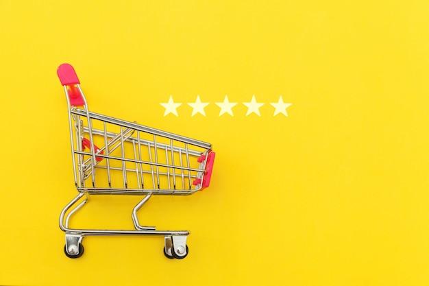 Carrinho de supermercado pequeno supermercado empurre compras brinquedo com rodas e classificação de 5 estrelas isolado em fundo amarelo. consumidor de varejo que compra o conceito de avaliação e revisão on-line.