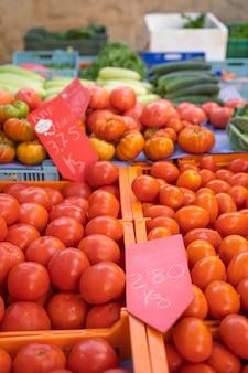 Carrinho de tomates vermelhos em cestas no mercado de pollensa em palma de maiorca, espanha vertical