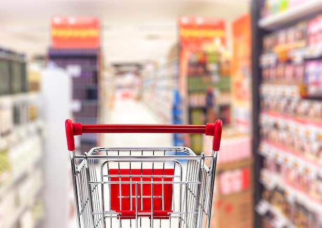 Carrinho de transporte no interior desfocado do supermercado para o conceito de negócio