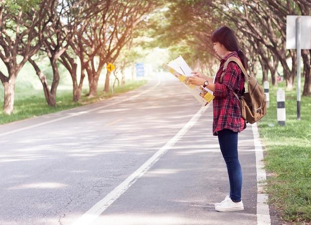 Carrinho de turista menina asiática olhar mapa na mão na estrada