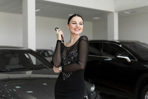 Carrinho de vendedor de carro ou mulher bonita, segurando uma chave remota de carro novo em uma sala de exposições de carros