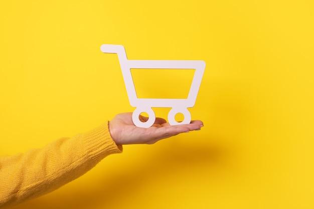 Carrinho disponível sobre fundo amarelo, conceito de compra online