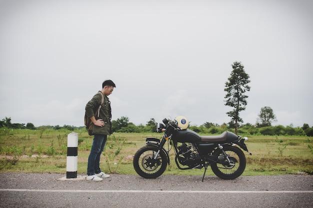 Carrinho do homem do motociclista que olha sua motocicleta (motocicleta) na rua e bonita.