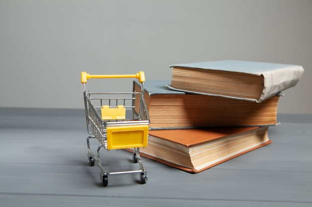 Carrinho e livros sobre a mesa. conceito de comprar livros em fundo cinza