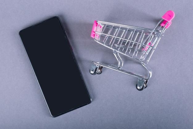 Carrinho e smartphone preto isolado em fundo cinza. conceito de compras online.