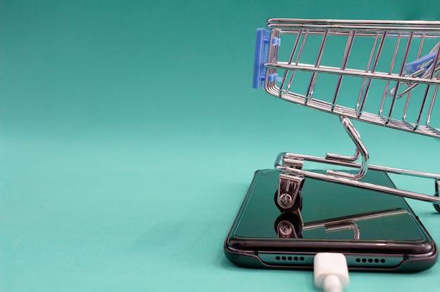Carrinho e telefone sobre um fundo verde com reflexão vendas e conceitos de compras.