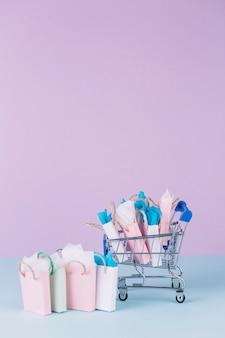 Carrinho em miniatura cheio de sacolas de papel