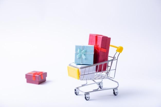 Carrinho em miniatura com presentes em um fundo branco. conceito de compras de férias. fechar-se.