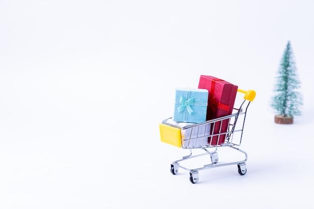 Carrinho em miniatura com presentes em um fundo branco. conceito de compras de natal e ano novo. fechar-se.