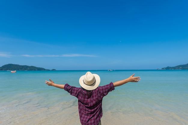 Carrinho feliz da mulher do curso na areia do mar com o céu azul no dia ensolarado.