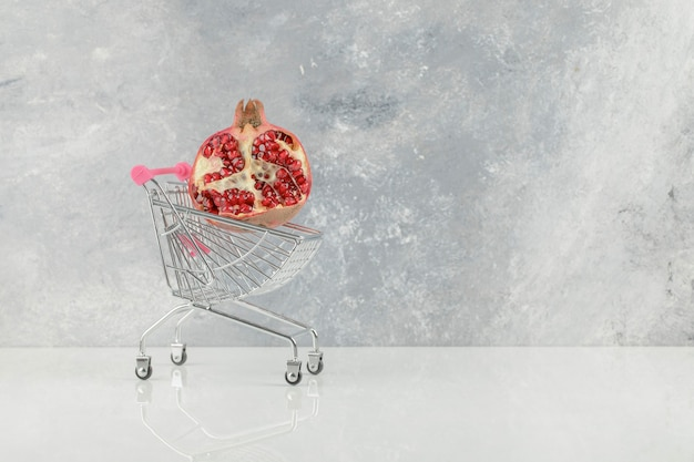 Carrinho pequeno com romãs vermelhas frescas na mesa branca.