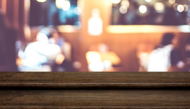 Carrinho vazio de comida de mesa de madeira escura passo com borrão pessoas que jantam no café restaurante