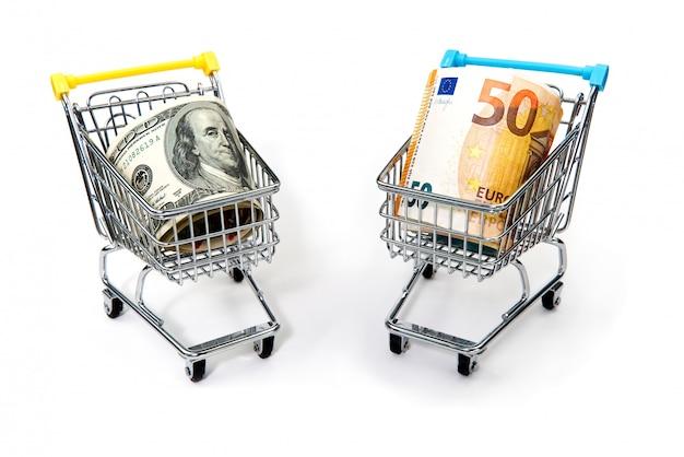 Carrinhos de compras cheios de notas de euro e dólar isoladas no branco.