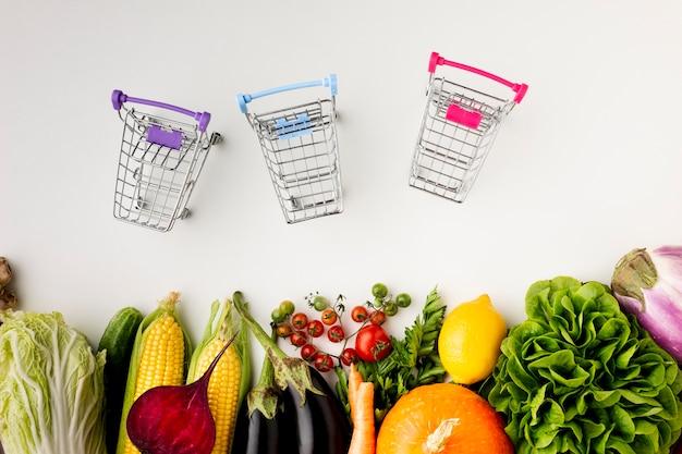 Carrinhos de compras com vista superior e deliciosos legumes
