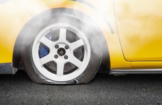 Carro amarelo com um pneu furado nas roas
