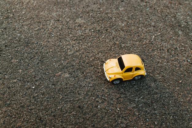 Carro amarelo do brinquedo na praia na luz solar no verão.