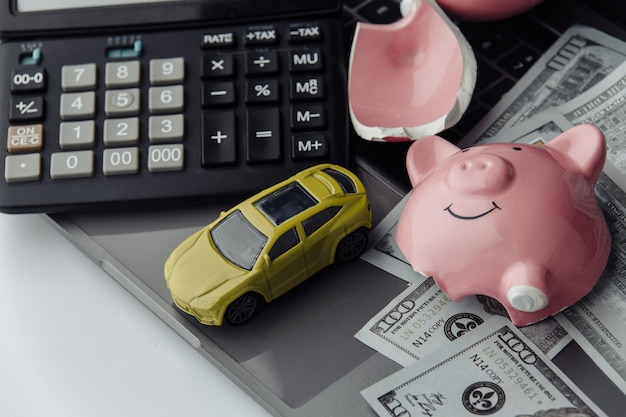 Carro amarelo e notas de dólares com cofrinho quebrado. conceito de seguro