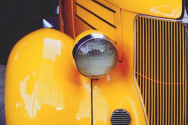 Carro amarelo retrô velho brilhante close-up