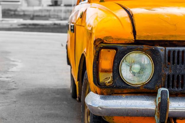 Carro antigo amarelo. fechar-se. quebrado.
