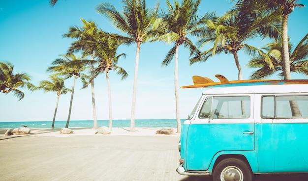 Carro antigo estacionado na praia tropical com uma prancha de surf no telhado