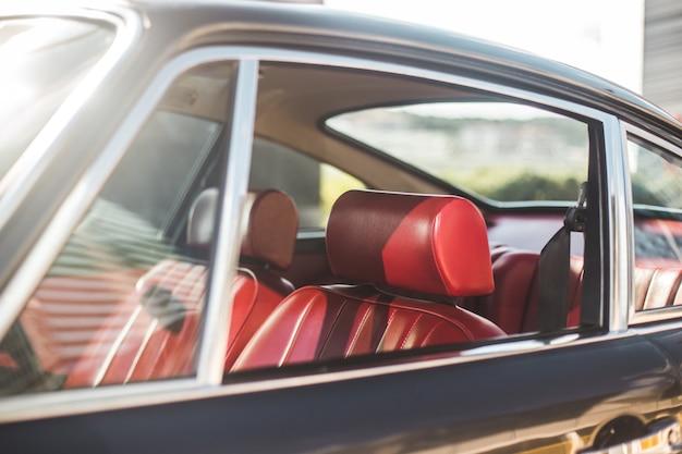 Carro antigo na exposição de automóveis, interior vermelho e assentos