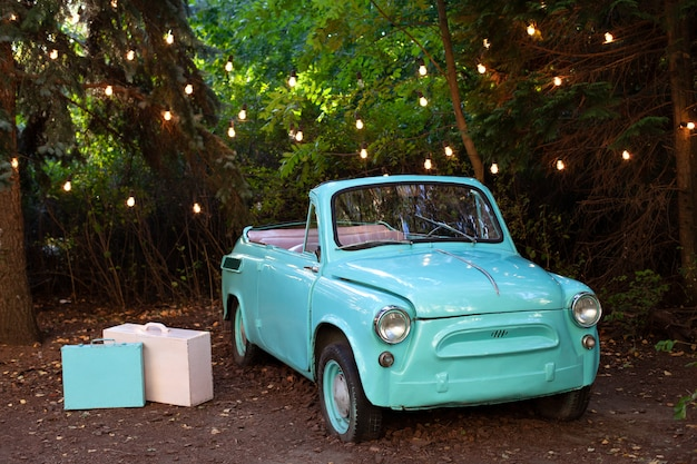 Carro antigo pequeno retrô em pé no jardim no verão em uma festão de parede, queima de lâmpadas. carro clássico decoração de casamento. decoração de casa e jardim para férias. photozone. viagem, viagem de verão