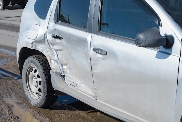 Carro após um acidente com danos ao corpo, do lado de fora. amassados e arranhões na porta traseira e no pára-choque de um carro, close-up. acidente de trânsito
