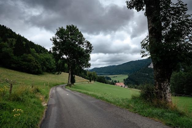 Carro azul na bela maneira com o fundo da estrada para a floresta. conceito de viagens de estrada temporada carro viagem. estilo de grão de tom de filme de fotografia cinematográfica