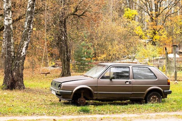 Carro bege abandonado sem roda, no fundo da natureza do outono