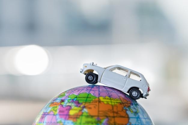 Carro branco do brinquedo na mini esfera do mapa de mundo.