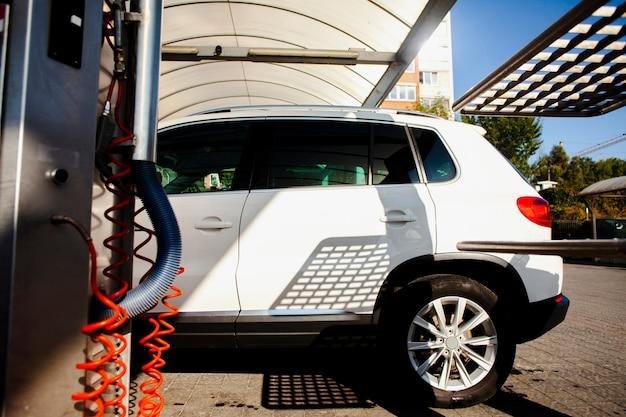 Carro branco entrando em uma lavagem de carro