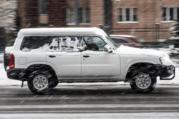 Carro branco grande fora da estrada que monta no movimento da velocidade na rua no inverno debaixo da neve
