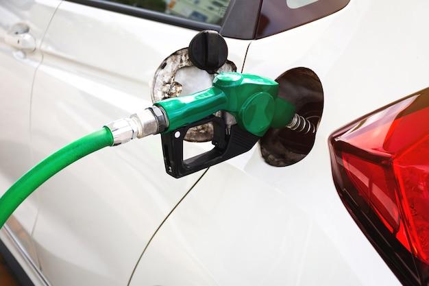 Carro branco reabastecendo no posto de gasolina com bico de combustível verde.