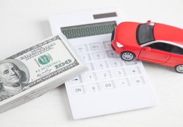 Carro, calculadora e dinheiro em fundo branco.