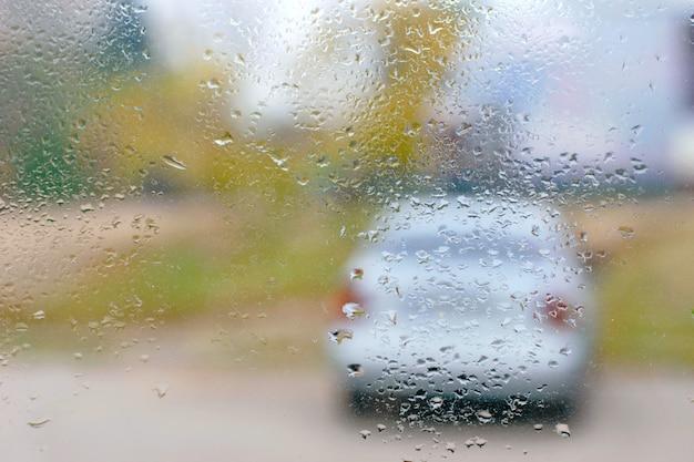 Carro cinza atrás da janela molhada com gotas de chuva, bokeh rua turva.