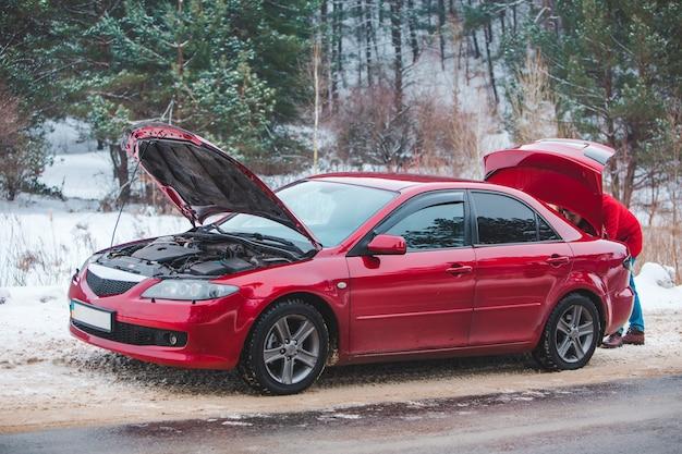 Carro com capô aberto homem olhando em quebra de porta-malas na estrada temporada de inverno