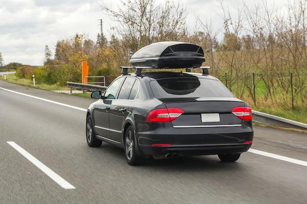 Carro com contêiner de caixa de bagagem de teto para viajar em uma estrada