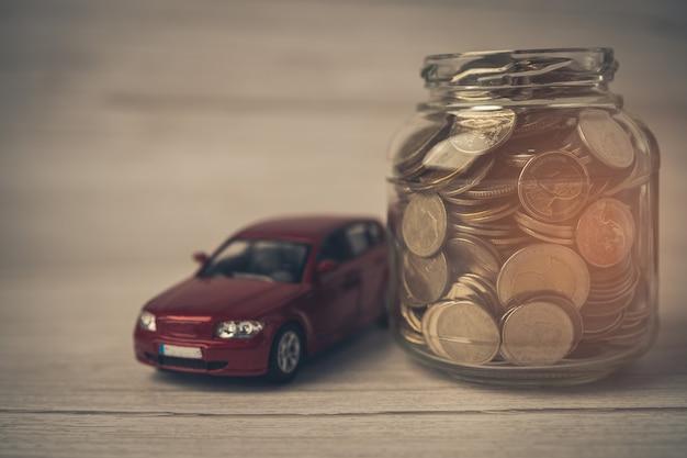 Carro com moedas financiamento de empréstimo de carro economizando dinheiro, seguro e conceitos de tempo de leasing